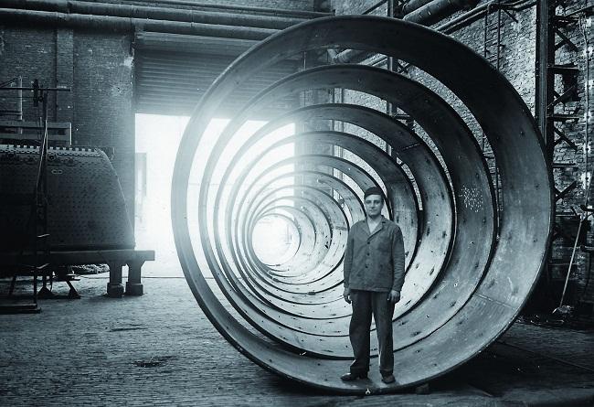 1.3 Operaio in fabbrica dentro a delle sezioni di tubo